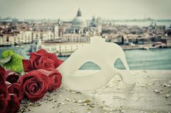 Image de masque vénitien élégant et de roses rouges au-dessus de table en bois devant le fond trouble de Venise Photo libre de droits