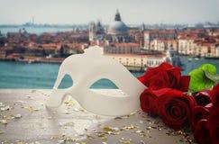 Image de masque vénitien élégant et de roses rouges au-dessus de table en bois devant le fond trouble de Venise Images stock