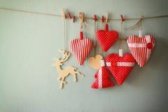 Image de Noël des coeurs de tissu et de l'arbre rouges, renne en bois, accrochant sur la corde devant le fond en bois bleu Rétro  Photo libre de droits