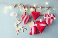 Image de Noël des coeurs et de l'arbre rouges de tissu lumières en bois de renne et de guirlande, accrochant sur la corde Images libres de droits