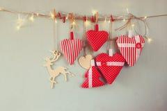 Image de Noël des coeurs et de l'arbre rouges de tissu lumières en bois de renne et de guirlande, accrochant sur la corde Photo libre de droits