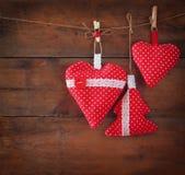 Image de Noël des coeurs rouges et de l'arbre de tissu accrochant sur la corde devant le fond en bois Rétro filtré Photos libres de droits