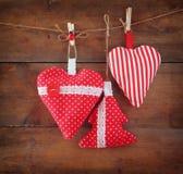 Image de Noël des coeurs rouges et de l'arbre de tissu accrochant sur la corde devant le fond en bois Rétro filtré Images stock
