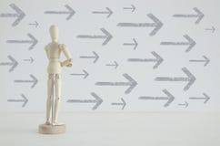 Image de personne en bois se tenant avec le sien de retour devant le fond texturisé complètement des flèches se dirigeant dans le Image stock