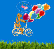 Image de petit homme décoratif sur une bicyclette et des ballons contre le ciel Image stock