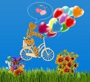 Image de petit homme décoratif sur une bicyclette et des ballons contre le ciel Images stock
