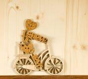 Image de petit homme décoratif sur une bicyclette sur le fond de conseils en bois Image libre de droits