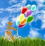 Image de petits homme et ballons décoratifs sur une bicyclette contre le ciel Image stock
