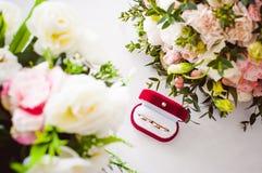 Image de photo d'une boîte rouge de velours avec des anneaux de mariage des jeunes mariés Image stock