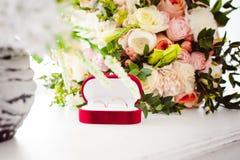 Image de photo d'une boîte rouge de velours avec des anneaux de mariage des jeunes mariés Photographie stock