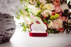 Image de photo d'une boîte rouge de velours avec des anneaux de mariage des jeunes mariés Photo stock