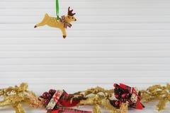 Image de photographie de Noël de décoration de Noël raccrochant du renne de la pâte avec le fond de fête de Noël d'or sur le bois Photographie stock libre de droits