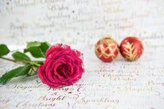 Image de photographie de Noël des roses rouges avec des pétales de scintillement et des babioles rouges d'or dans la distance sur Image stock