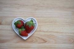 Image de photographie de nourriture des fraises rouges saines dans un plat blanc de forme de coeur d'amour sur le fond en bois av Photographie stock libre de droits