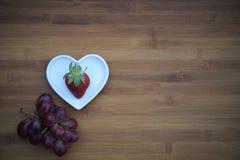 Image de photographie de nourriture de la fraise saine dans le plat de forme de coeur d'amour avec des raisins pourpres et le fon Photo libre de droits