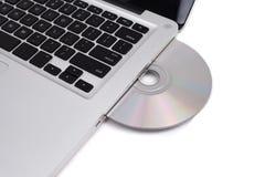 Image de plan rapproché d'un ordinateur portatif et d'un disque compact-ROM Photographie stock libre de droits