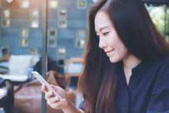 Image de plan rapproché d'une belle femme asiatique avec le visage souriant à l'aide et regardant du téléphone intelligent Photo stock