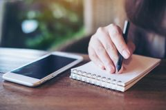 Image de plan rapproché d'une femme tenant le crayon et écrivant sur le carnet avec le téléphone portable blanc sur la table en b Photographie stock libre de droits