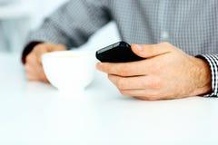 Image de plan rapproché d'une main masculine dactylographiant sur le smartphone Photographie stock libre de droits