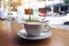 Image de plan rapproché d'une tasse blanche de café de latte sur la table en bois en café Photo stock