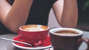 Image de plan rapproché d'une tasse de café de latte et d'un café d'Americano avec la femme s'asseyant en café Photographie stock libre de droits