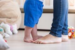 Image de plan rapproché des pieds du ` s de bébé garçon de 10 mois se tenant avec la mère Images stock