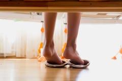 Image de plan rapproché de dessous le lit des pieds femelles utilisant des pantoufles Images stock