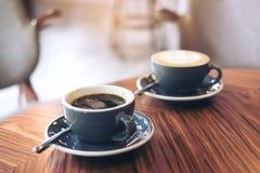 Image de plan rapproché de deux tasses bleues de café chaud de latte et de café d'Americano sur la table en bois de vintage Image libre de droits