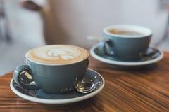 Image de plan rapproché de deux tasses bleues de café chaud de latte et de café d'Americano sur la table en bois de vintage Photo libre de droits