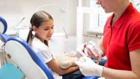 Image de plan rapproché de fille de enseignement de dentiste pédiatrique au sujet d'hygiène de dent photo libre de droits