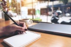 Image de plan rapproché de l'écriture de main du ` s de femme d'affaires sur un carnet vide avec la tasse d'ordinateur portable e Photo stock