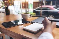 Image de plan rapproché de l'écriture de main du ` s de femme sur un carnet vide avec l'ordinateur portable, comprimé Image stock