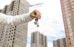 Image de plan rapproché de main d'homme d'affaires jugeant des clés de nouvelle maison contre des maisons en construction Image libre de droits