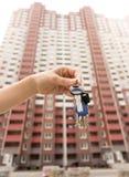 Image de plan rapproché de main femelle jugeant des clés de nouvel appartement contre la grande maison en construction Photo stock