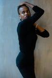 Image de portrait de femme afro-américaine sérieuse dans une robe noire se tenant avec des bras au-dessus de sa tête, d'isolement images stock