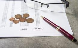 Image de profits et pertes de concept d'un stylo, d'une calculatrice et des pièces de monnaie sur les documents financiers photo stock