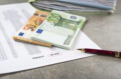 Image de profits et pertes de concept d'un stylo, d'une calculatrice et des pièces de monnaie sur les documents financiers image stock