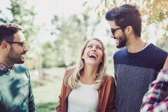 Image de quatre jeunes amis de sourire heureux marchant dehors en parc Photos stock