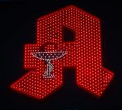 Image de signe allemand lumineux rouge de pharmacie avec le fond foncé images libres de droits