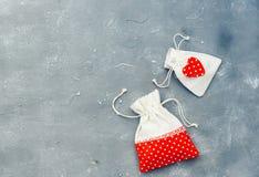 Image de thème de Gifting avec une poche à carreaux de tissu et un coeur rouge décoratif photos stock