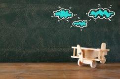 Image de vieux jouet en bois d'avion sur la table en bois devant l'ensemble de graphiques d'infos au-dessus de tableau texturisé Photo libre de droits