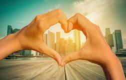 Image de vintage de main en forme de coeur avec la ville brouillée de Singapour Photo libre de droits