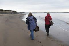 Image de vue arrière d'un couple femelle mûr marchant le long de la plage Images stock