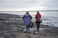 Image de vue arrière d'un couple femelle mûr marchant le long de la plage Images libres de droits
