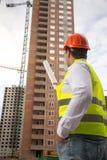 Image de vue arrière de l'architecte masculin se dirigeant aux bâtiments en construction avec le rouleau de modèles Photo libre de droits