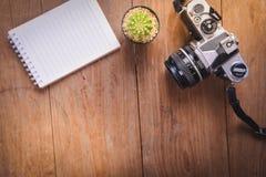 image de vue supérieure de carnet ouvert avec les pages vides et le cactus et d'appareil-photo sur la table en bois Photographie stock
