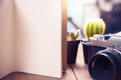 image de vue supérieure de carnet ouvert avec les pages vides et le cactus deux et d'appareil-photo sur la table en bois Photos libres de droits