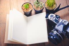 Image de vue supérieure de carnet ouvert avec les pages vides et le cactus trois et d'appareil-photo sur la table en bois Images stock