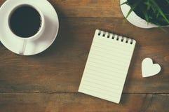 Image de vue supérieure de carnet à côté de tasse de café et de peu de coeur en bois vintage filtré et modifié la tonalité Photos libres de droits