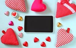 Image de vue supérieure de comprimé, chocolats colorés de forme de coeur, coeurs de tissu sur le fond en bois Concept de célébrat Photos stock